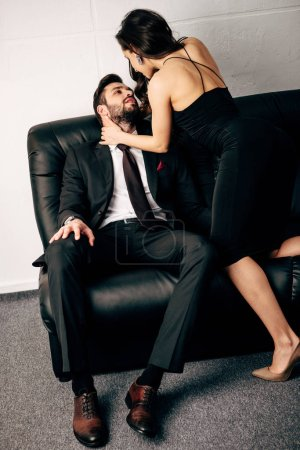 Photo for Attractive girl in black dress looking at bearded man in suit sitting on sofa - Royalty Free Image