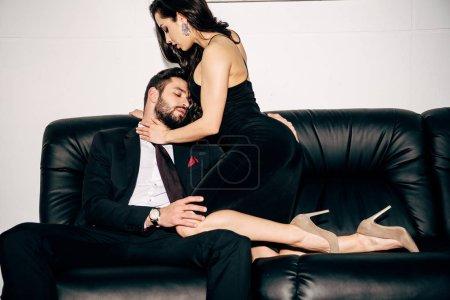Photo pour Homme passionné assis sur le canapé et touchante fille sexy en robe noire - image libre de droit