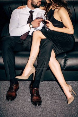 Photo for Cropped view of bearded man and girl in black dress sitting on sofa and holding glasses of wine - Royalty Free Image