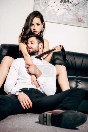 Photo for Beautiful woman sitting on sofa and holding tie of handsome boyfriend with closed eyes - Royalty Free Image