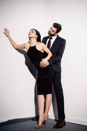 Photo for Brunette woman in black dress holding hands with man near white wall - Royalty Free Image