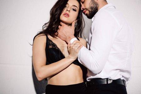 Photo pour Bel homme touchant le visage de la femme brune sexy en soutien-gorge noir debout sur blanc - image libre de droit