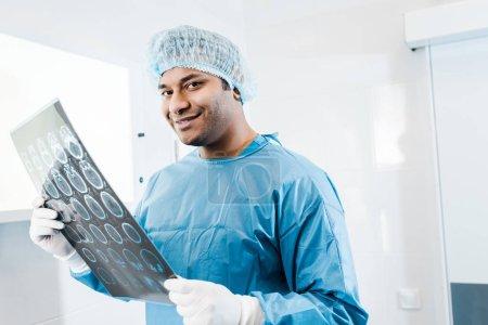 Photo pour Médecin souriant en uniforme et casquette médicale tenant des rayons X et regardant la caméra - image libre de droit