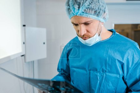 selective focus of good-looking doctor in medical cap and uniform holding x-ray