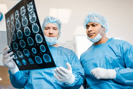 Photo for Handsome doctors in uniforms and medical masks talking about x-ray in clinic - Royalty Free Image