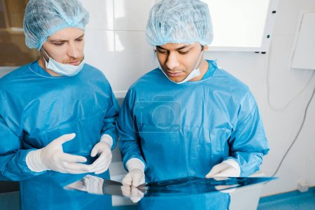 good-looking doctors in uniforms and medical masks talking about x-ray