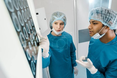 Photo pour Beau et beau médecin en uniformes et masques médicaux pointant avec les doigts à rayons x - image libre de droit