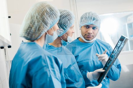 Photo for Selective focus of doctors in uniforms and medical masks talking about x-ray - Royalty Free Image