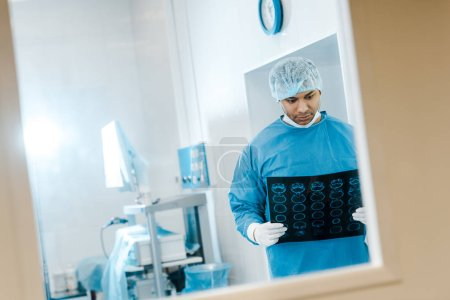 Photo for Handsome doctor in uniform and medical cap holding x-ray in clinic - Royalty Free Image