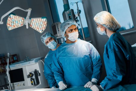 Photo for Doctors and nurse in uniforms and medical masks talking in operating room - Royalty Free Image