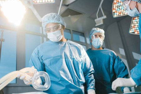 Photo for Doctors and nurse in uniforms and medical caps holding mask in operating room - Royalty Free Image