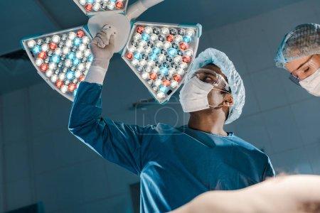 Photo pour Médecin et infirmière en uniformes et casquettes médicales préparant à l'opération - image libre de droit