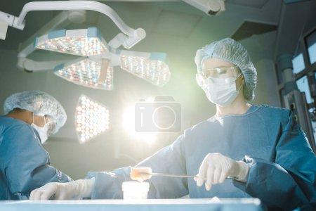 Photo pour Chirurgien faisant une opération et infirmière en uniforme tenant tampon dans la salle d'opération - image libre de droit