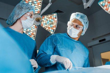 Photo pour Infirmière en uniforme et chirurgien en bonnet médical se regardant dans la salle d'opération - image libre de droit
