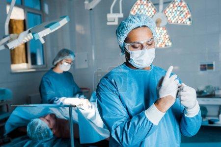 Photo pour Focus sélectif du médecin en uniforme mettre hors gants en latex dans la salle d'opération - image libre de droit
