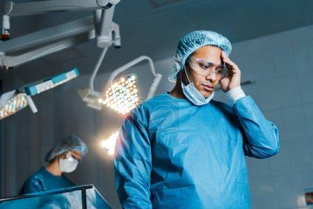 Photo pour Focus sélectif du médecin en uniforme et masque médical regardant vers le bas dans la salle d'opération - image libre de droit