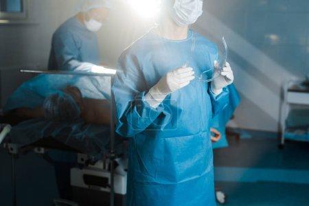 Photo pour Vue recadrée de l'infirmière en uniforme et masque médical tenant des lunettes dans la salle d'opération - image libre de droit