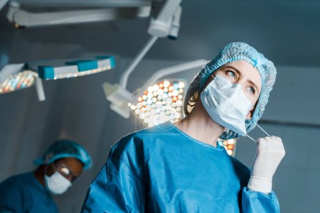Photo for Selective focus of nurse in uniform putting off medical mask in operating room - Royalty Free Image