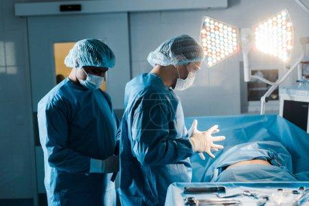 Photo pour Infirmière et médecin en uniforme et masques médicaux en salle d'opération - image libre de droit
