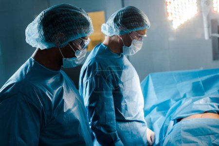 Photo for Nurse and doctor in uniforms and medical masks in operating room - Royalty Free Image