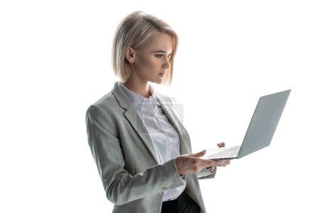 Foto de Pretty, blond, attentive businesswoman holding laptop isolated on white - Imagen libre de derechos