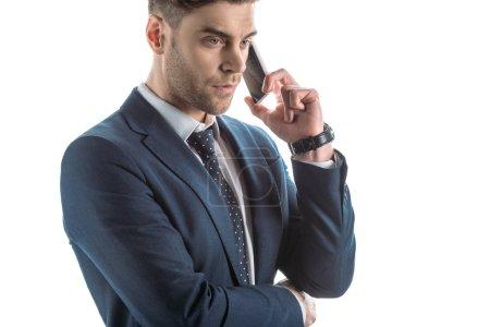 Photo pour Beau, homme d'affaires sérieux parlant sur le smartphone isolé sur le blanc - image libre de droit