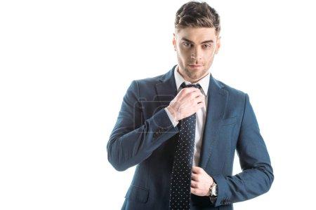 Foto de Handsome, confident businessman in suite touching tie isolated on white - Imagen libre de derechos