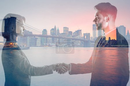 Photo pour Double exposure of man and woman shaking hands and looking at each and new york evening cityscape - image libre de droit