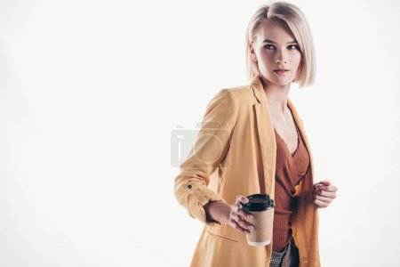 Photo pour À la mode, jolie femme avec le cheveu blond retenant la tasse de papier sur le gris - image libre de droit