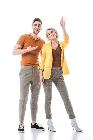 Foto de Cheerful young woman waving hand while standing near handsome man isolated on white - Imagen libre de derechos