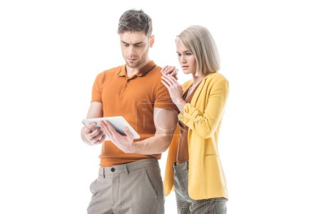Photo for Serious blonde woman and thoughtful handsome man using digital tablet together isolated on white - Royalty Free Image