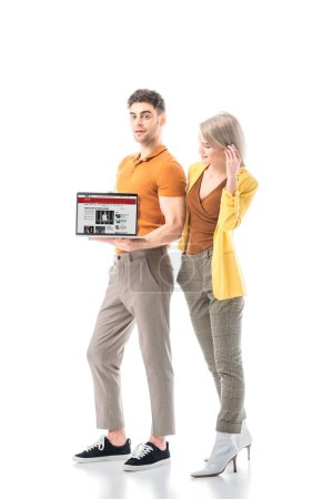 Foto de Handsome man holding laptop with bbc news website on screen while standing near attractive woman isolated on white - Imagen libre de derechos