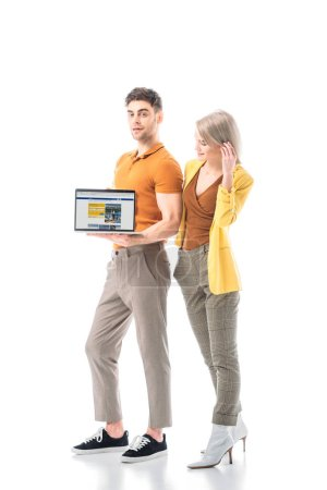 Foto de Handsome man holding laptop with booking website on screen while standing near pretty woman isolated on white - Imagen libre de derechos