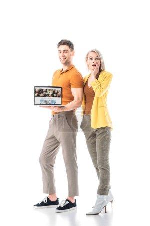 Photo pour Homme gai retenant l'ordinateur portatif avec le site Web de depositphotos sur l'écran tout en restant près de la femme étonnée d'isolement sur le blanc - image libre de droit
