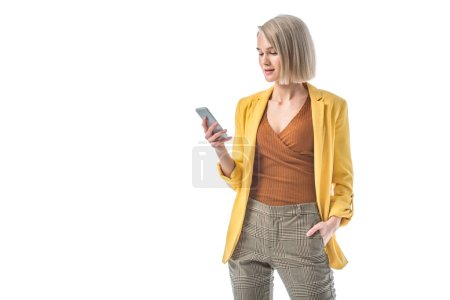 Photo for Attractive woman with hand in pocket holding smartphone isolated on white - Royalty Free Image