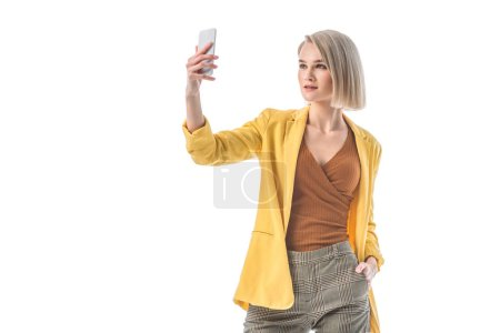 Photo for Beautiful blonde woman taking selfie with smartphone isolated on white - Royalty Free Image