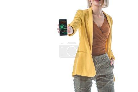 Photo pour Vue partielle de la femme avec la main dans le smartphone de fixation de poche avec l'application d'analyse de marketing sur l'écran d'isolement sur le blanc - image libre de droit