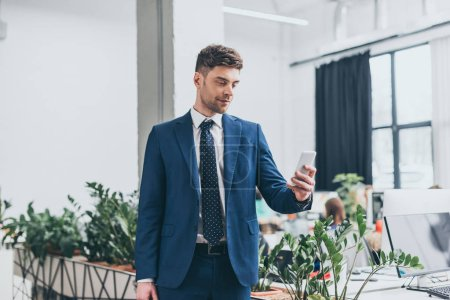 good-looking, smiling businessman in suite using smartphone in office
