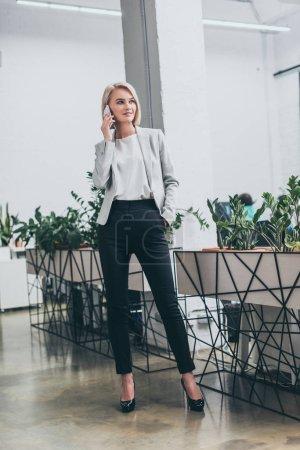 beautiful blonde businesswoman talking on smartphone in office