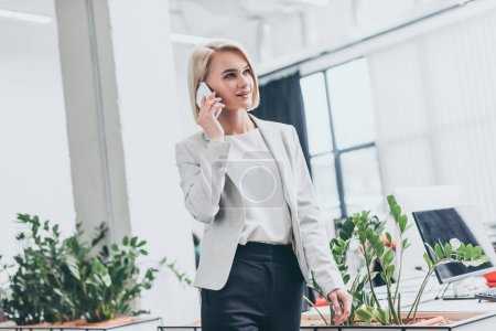 Photo for Attractive blonde businesswoman in formal wear talking on smartphone in office - Royalty Free Image