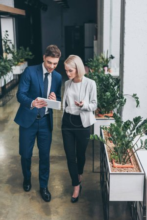 Photo pour Deux jeunes partenaires commerciaux utilisant ensemble une tablette numérique au bureau - image libre de droit