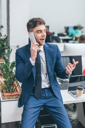 Photo for Cheerful businessman holding talking on smartphone and gesturing in office - Royalty Free Image