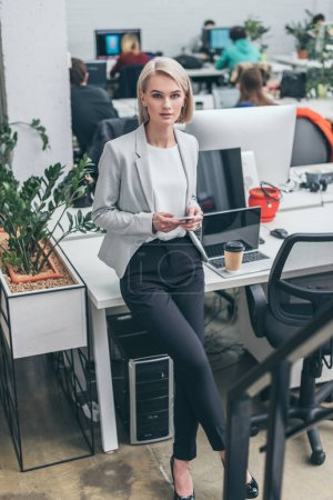 pretty blonde businesswoman in formal wear standing by workplace and looking at camera