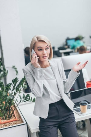 attractive smiling businesswoman talking on smartphone and gesturing in office
