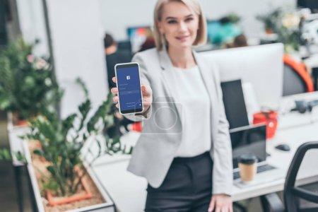 Selektiver Fokus der hübschen Geschäftsfrau mit Smartphone und Facebook-App auf dem Bildschirm