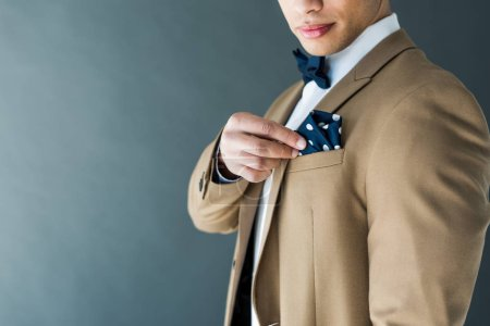 cropped view of stylish mixed race man in suit adjusting napkin isolated on grey with copy space