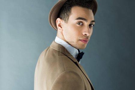 élégant homme mixte élégant en costume et chapeau regardant la caméra isolée sur gris