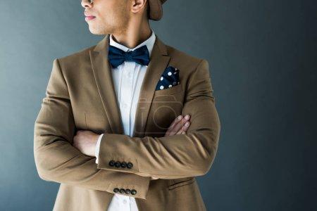 Foto de Vista recortada del elegante hombre de raza mixta en traje con brazos cruzados aislados en gris - Imagen libre de derechos