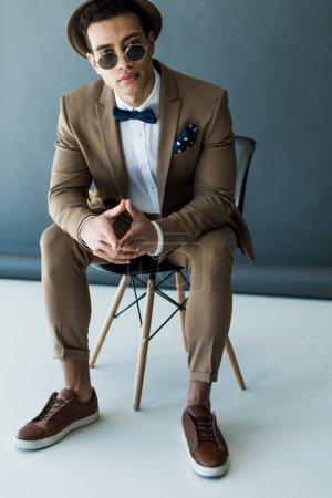 Stilvoller Mischling in Anzug und Sonnenbrille sitzt auf Stuhl und blickt in die Kamera auf grau-weiß