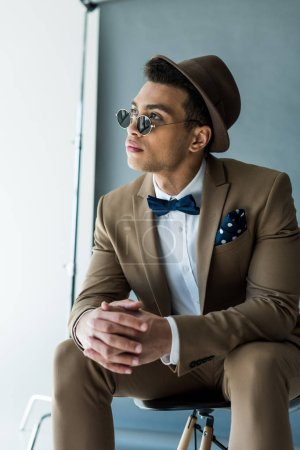 stylish mixed race man in suit and sunglasses sitting on chair and looking away